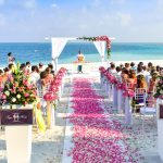 A seaside wedding with a rose walkway